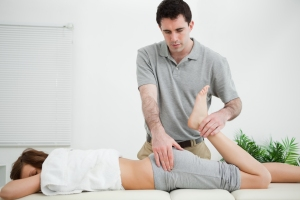 Woman lying while being stretched by a physiotherapist in a room